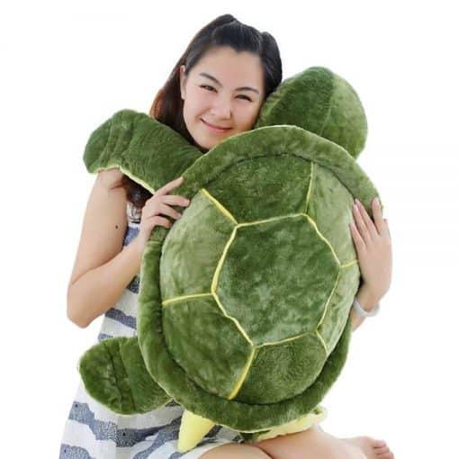 Femme tenant une peluche tortue verte