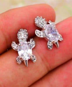 Boucles d'oreilles tortue en zircon blanc sur une main