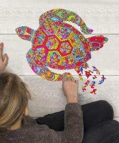 une fille réalisant un puzzle en forme de tortue