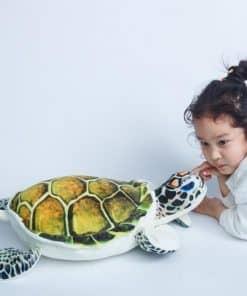 fillette joue avec une peluche tortue de mer