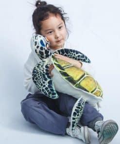 fillette caline une peluche tortue de mer