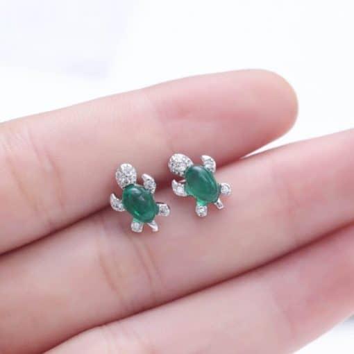 Petites boucles d'oreille tortue Jade dans une main